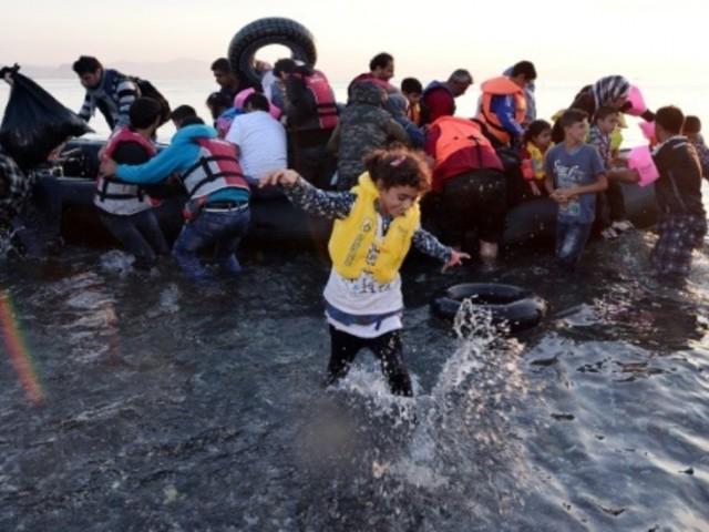 Des migrants syriens arrivent a bord d un canot pneumatique sur une plage de l'île grecque de Kos le 15 aout 2015